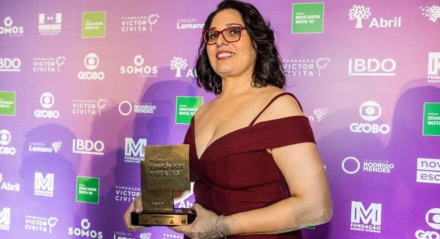 Rutemara segurando o troféu do Prêmio Educador Nota 10