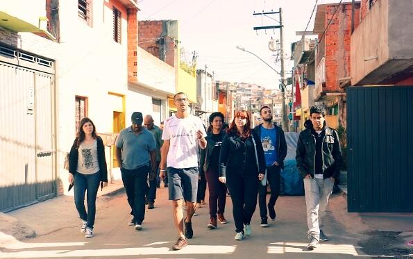 Visitantes são conduzidos por Edu durante visita à favela