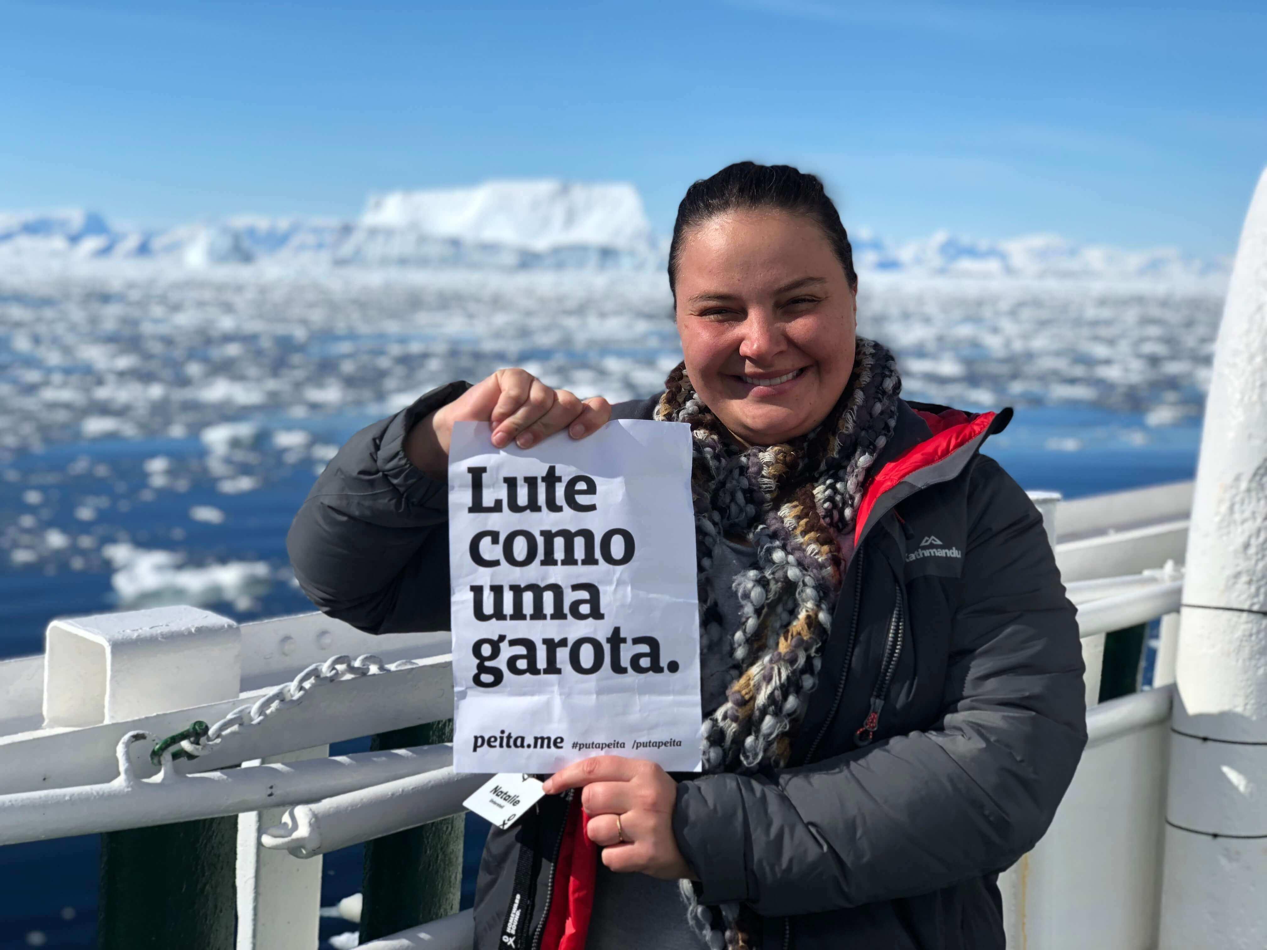 Natalie na Antártida com o cartaz escrito Lute como uma Garota